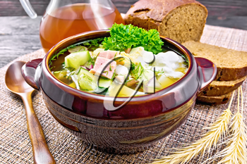 Cold soup okroshka from sausage, potato, egg, radish, cucumber, greens and drink of kvass in a clay bowl, bread on wicker napkin on background of dark wooden board