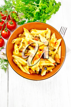 Penne pasta with eggplant and tomatoes in a bowl on towel, fork, garlic and parsley on a wooden plank background from above
