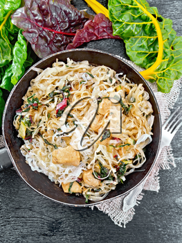 Rice noodles with leafy beet, chicken breast meat, cashew nuts and soy sauce in a frying pan on burlap on the background of black wooden board from above