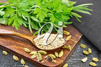 Ground cardamom in a spoon, seasoning capsules, napkin, fresh parsley and rosemary on wooden board background