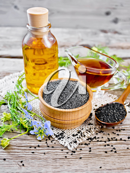 Flour of black caraway in a bowl, seeds in a spoon, oil in a bottle and sauceboat on burlap, sprigs of Nigella sativa with blue flowers and green leaves on wooden board