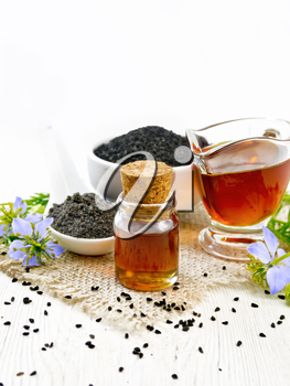 Nigella sativa oil in vial and gravy boat, seeds in a spoon and black cumin flour in a bowl on burlap, kalingi twigs with blue flowers and leaves on wooden board background