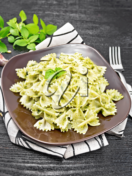 Farfalle pasta with pesto, basil in a plate on a napkin against dark wooden board