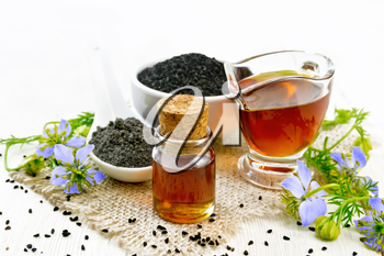 Nigella sativa oil in vial and gravy boat, seeds in a spoon and black cumin flour in a bowl on burlap, kalingi twigs with blue flowers and leaves on light wooden board background