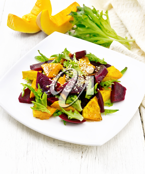 Baked pumpkin, boiled beetroot, arugula salad seasoned with vinegar, spices, orange juice and vegetable oil in a plate, napkin on white wooden board background