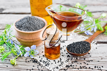 Nigella sativa oil in vial, gravy boat and bottle, seeds in a spoon and black cumin flour in a bowl on burlap, kalingi twigs with blue flowers and green leaves on wooden board background