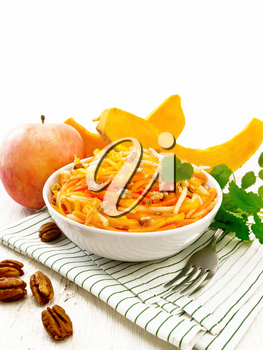 Pumpkin, carrot and apple salad with pecans seasoned with vegetable oil in a bowl on a towel, mint on light wooden board background