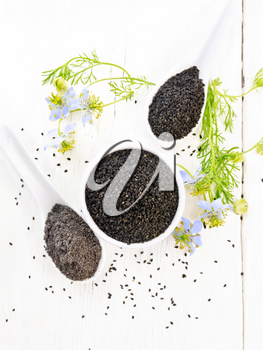 Black cumin seeds in a bowl, flour and seeds in spoons, kalingi sprigs with blue flowers and leaves on a light wooden board background from above