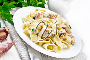 Tagliatelle pasta with salmon, cream, garlic and herbs in a plate on a napkin, fork, parsley and basil on white wooden board background