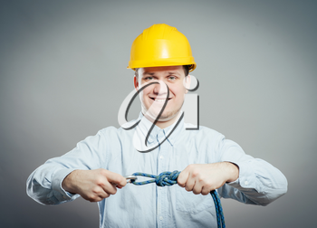 Construction worker holds a rope and carbine. Full length studio shot isolated .