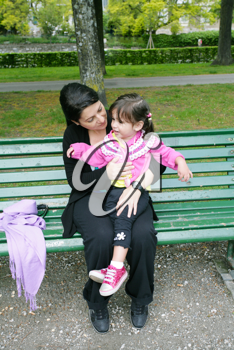 Portrait of smiling mother and little daughter hugging in the park
