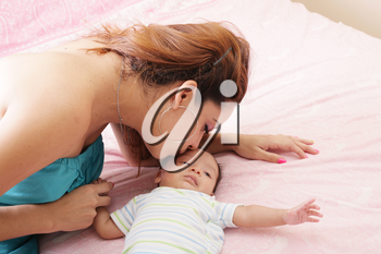 Young mother kissing her small newborn