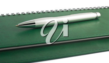 Royalty Free Photo of a Metal Pen Sitting on a Spiral Notebook