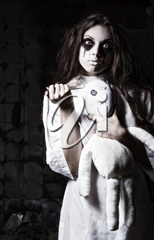 Horror style shot: a strange crazy girl with moppet doll and needle in hands