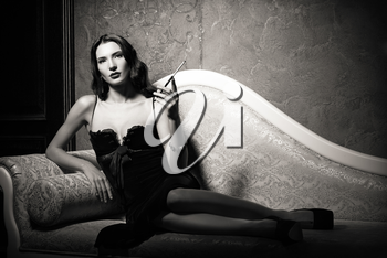 Film noir style: dangerous elegant young woman lying on a sofa and smoking cigarette. Black and white