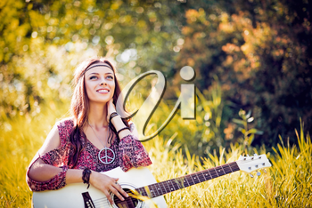 Portrait of a beautiful smiling hippie girl with guitar. Outdoor shot