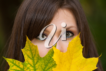 Royalty Free Photo of a Woman Covering Her Face With Leaves