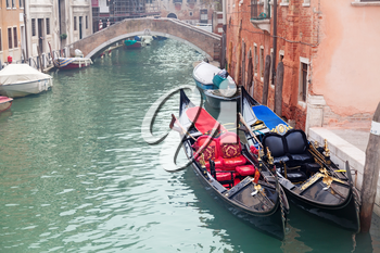 Two gondola in Venice near pier and golden figurines