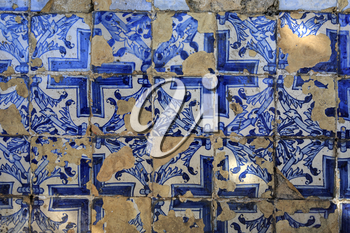 Blue portuguese tiles on the wall with cracks