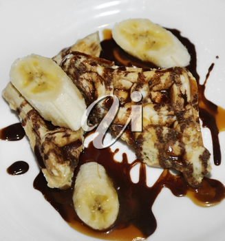 Waffles With Bananas And Chocolate Syrup For Breakfast