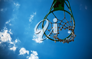 Old basketball basket with a cloudy blue sky in the background.