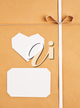 Hand made paper tag and heart on kraft paper as background. Greeting card