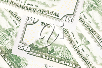 A stack of fifty 50 dollar bills fanned out with the back US Capitol showing on a white background