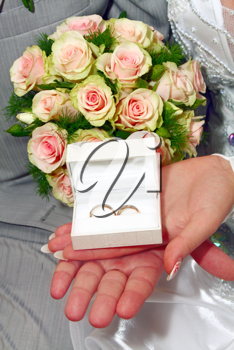 two wedding rings in white box and bouquet for fiance and fiancee