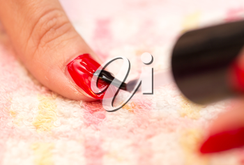 nails painted red nail polish in a beauty salon