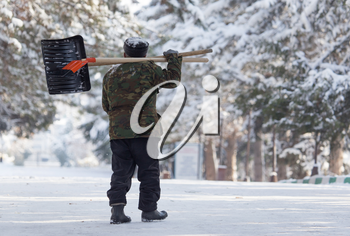 Worker cleans snow shovel in the nature