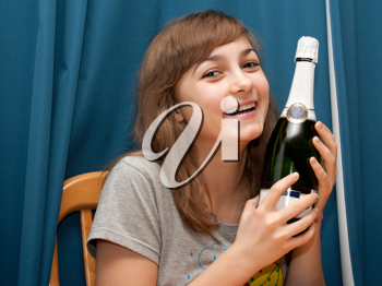 Royalty Free Photo of a Girl Holding a Bottle of Champagne