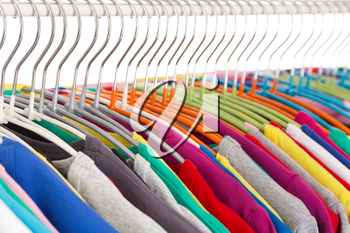Collection of colored shirts on steel hangers. Isolate. Shallow depth of field.