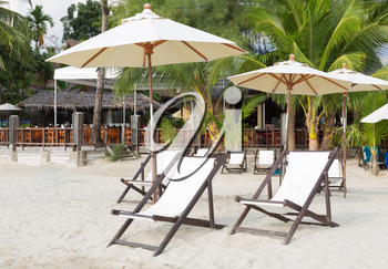 Sun beds and umbrellas on the beach on a background of the jungle