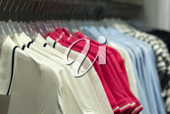 Fashionable clothes on hangers in store.
