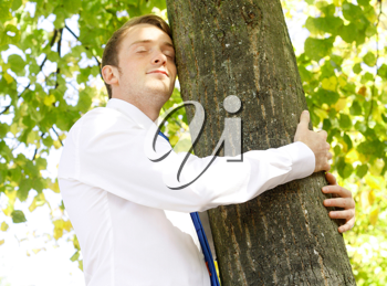 Royalty Free Photo of a Businessman Hugging a Tree