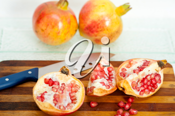 fresh pomegranate fruit over wood cutting board with knife