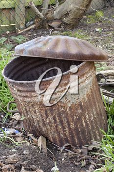 Abandoned rusty old trashcan half buried in the ground