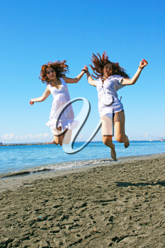 Royalty Free Photo of Two Women Jumping on the Beach