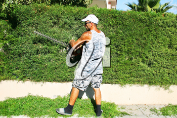 Royalty Free Photo of a Gardener Trimming a Bush