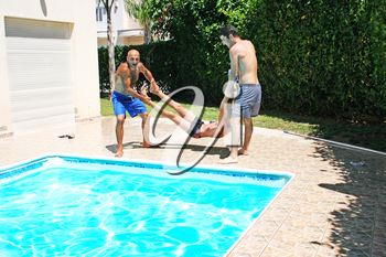 Royalty Free Photo of People Throwing Their Friend into a Pool