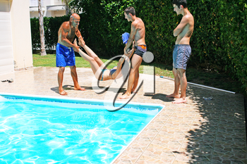 Royalty Free Photo of People Throwing Their Friend into a Swimming Pool