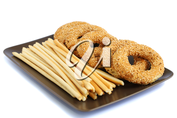 Round rusks and bread sticks on plate isolated on white background.