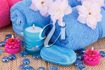 Spa set with towels, candles, soaps and flowers on bamboo background.