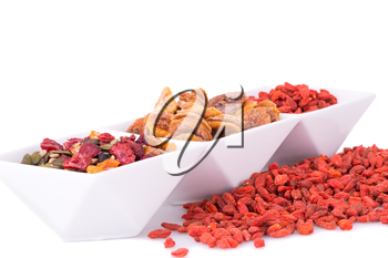 Dried fruits, berries and seeds in bowl on white background.