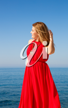 Blond woman in the red dress at the beach in Cyprus.