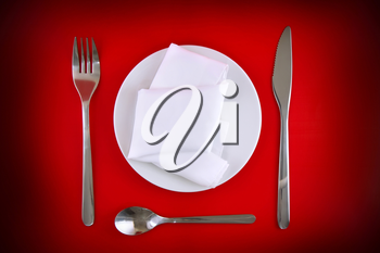 Table serving-knife,plate,fork and silk napkin  on  red colour background.