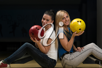 Cheerful Young Couple Holding Bowling Ball