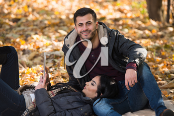 Beautiful Young Couple Sitting In The Park On A Beautiful Autumn Day - They Are Using Internet Via Digital Tablet