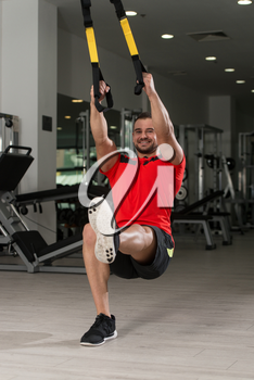 Fitness Instructor Exercising Crossfit With Trx Fitness Straps In The Gym's Studio