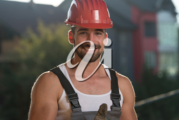 Portrait Of A Construction Worker With Red Helmet Making Thumbs Up Sign